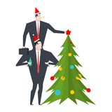 New Year corporate party. Businessman decorates Christmas tree. Royalty Free Stock Image