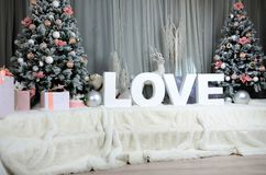 New year cozy interior with a large plush veil, two Christmas trees, toy forest animals and the inscription love of big white lett. Ers Stock Photo