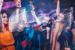 New Year dance party in motion. Happy friends company in night club, active Christmas celebration. Disco people in blurred colors, modern youth life, pickup Stock Photo