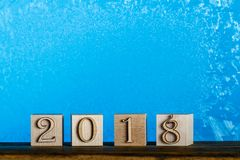 New year date 2018. Cubes of natural wood. Frozen window blue ba. Ckground. The sill of the window royalty free stock image