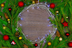 New year decoration. Chrismas lights surrounded by green branches from christmas tree decorated with colorful balls and cones Royalty Free Stock Photos