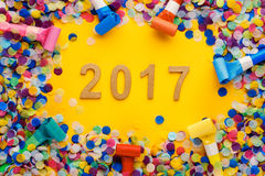 New year 2017 decoration. Confetti and whistles on yellow background Royalty Free Stock Images