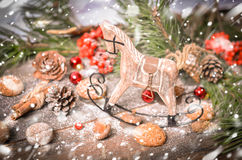 New Year Decoration with Vintage Wooden Horse. Christmas and New Year Decoration with Vintage Wooden Horse, Pine Branches, Oatmeal Cookies, Rowan, Walnuts, Fir Stock Images