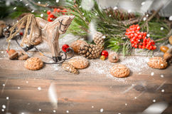 New Year Decoration with Vintage Wooden Horse. Christmas and New Year Decoration with Vintage Wooden Horse, Pine Branches, Oatmeal Cookies, Rowan, Walnuts, Fir Royalty Free Stock Photo