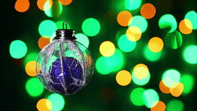 New Year decorations ball on blinking multicolor background Stock Photos