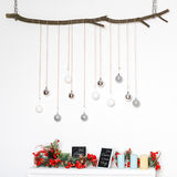New Year decorations with frosted red berries, candles and silver balls on tree branch. Royalty Free Stock Photo