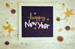 New Year decorations and objects flat lay photo with black chalkboard frame. And hand drawn inscription. Happy New Year 2017 gift lettering on black board royalty free stock photos