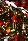 New year decorative toys on tree with lights and snow. Outdoors royalty free stock photography