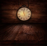 New Year design - Ticking clock. New Year's eve design - Ticking clock. Background with Wooden table with wooden wall with vintage clock close to midnight Royalty Free Stock Photos