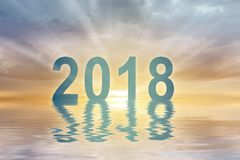 New year 2018 digits text sunset blur background. Happy new year 2018 digits text on sunset blur background reflecting in water Stock Photo
