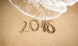 New Year 2016 digits written on seashore and being washed off. By wave Royalty Free Stock Photography