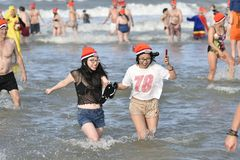 New year dive at Scheveningen 2018. SCHEVENINGEN, 1 January 2018 -Chinese tourists participate to the new year dive with full of happiness and joy running toward royalty free stock photo