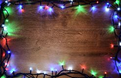 New-year electric garland on a wooden background. Bright bulbs on a wooden table and Christmas tree. stock images