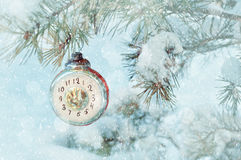 New Year eve background -New Year glass Christmas toy in the form of clock showing the New Year Eve, on snowy fir tree Royalty Free Stock Photos