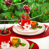 New Year eve banquet. Photo of New Year event banquet, beautiful white plates with Cristmas decoration on holiday setting table, decorated evergreen tree at home Stock Image