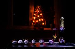 New Year Eve celebration background with pair of flutes and bottle of champagne with Christmas attributes (or elements) on snowy d Royalty Free Stock Photography