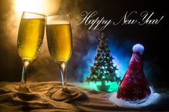 New Year Eve celebration background with pair of flutes and bottle of champagne with Christmas attributes (or elements) on snowy d stock images