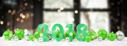 2018 new year eve with christmas baubles lined up 3D rendering. 2018 new year eve with green and white christmas baubles on snow background 3D rendering Royalty Free Stock Photography