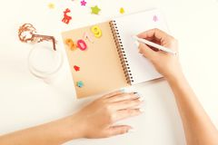 2019 New Year. Female hands writing New year`s resolutions. Opened notebook with Christmas decorations on white desk. Flat lay, stock image