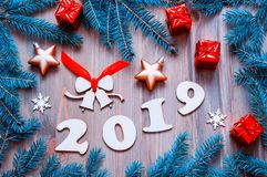 New Year 2019 festive background with 2019 figures, Christmas toys, blue fir tree branches and snowflakes royalty free stock images
