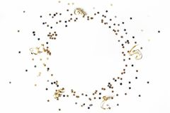 New Year festive composition. Circle made of black, silver and gold confetti stars and ribbons. Party decoration. Celebration concept. Flat lay, top view royalty free stock photography