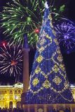 New Year fir-tree in garlands of fires at Palace Square and Christmas fireworks, St. Petersburg, Russia royalty free stock image