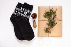 New year 2020 flat lay.Christmas black ornamental socks,gift box in eco kraft paper with pine tree cones.Winter holidays