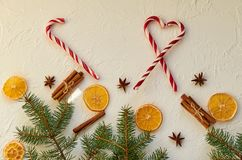 New year food decorations with fir branches, three red candy cones and traditional holiday spices: anise stars, sticks of cinnamon Stock Image