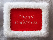 New Year frame with embroidered Merry Christmas. White fur New Year frame with red velvet and embroidered Merry christmas stock photography