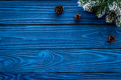 New year frame. Spruce branch and pine cones on blue wooden background top view copyspace Royalty Free Stock Image