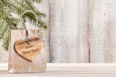 New Year gift bag with wooden heart shaped tag Royalty Free Stock Photo