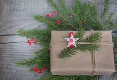 New year gift box handicraft wrapping, parchment, twine fir tree twigs, cute simple last minute present handmade.  Christmas Stock Photo