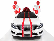 New year gift car. White luxury sedan with ballons. Isolated on white background Stock Photos