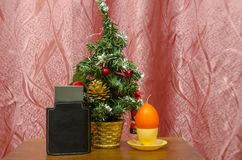 New Year gift still life. An artificial Christmas tree, an egg-shaped candle and a bottle of male toilet water royalty free stock photography