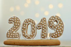 New Year 2019. Gingerbread figures on a wooden board. Christmas lights on the background. New Year greetings. Suitable as a backg. Round stock images