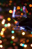 New Year glass of brandy in drunk person hand. Defocused image of cognac glass on Christmas tree lights background. Blurred abstract backdrop with bokeh festive stock images