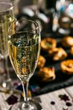 New Year: Glass Of Champagne With Party Food Behind Royalty Free Stock Image