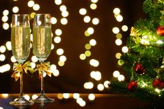 Merry Christmas and Happy New Year!. New Year glasses with champagne on the black reflecting surface stock image
