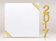 2017 New year glitter number and white card with gold ribbon in Stock Photo