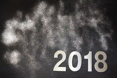 New Year 2018, glitters scattered, glisten and shimmer on a black background, copy space for your text.  stock photos