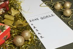 2019 New Year goals with blanco space in notebook surrounded with golden and red decoration. stock images