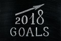 New Year 2018 goals with a rising arrow text chalk on a blackboard. Chalkboard written with text 2018 Goals. New year success in. Business. Plans for the year royalty free stock photo