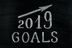 New Year 2019 goals with a rising arrow text chalk on a blackboard. Chalkboard written with text 2019 Goals. New year success in stock image