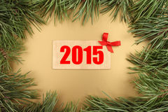 New Year gold background. Christmas fir tree and wooden plate with text 2015 Stock Photography