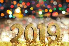2019 new year. 2019 golden figures standing in front of colorful blur lights background stock image