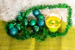 New year, green balls and decorations for the Christmas tree. Bright and beautiful scenery on a lemon background with white tinsel. And beads. Christmas winter royalty free stock photography