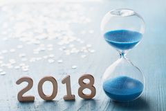 New year 2018 greeting card. Hourglass or sandglass on blue wooden table. Stock Photography