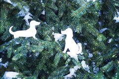 Happy new 2018 year of dog. New Year greeting card with paper dog figures on fir tree green branches with snow stock images