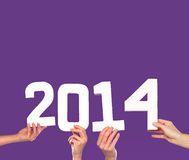 2014 New Year greeting card on purple. 2014 New Year greeting card with female hands holding up white numbers forming the date on a purple background with Stock Images