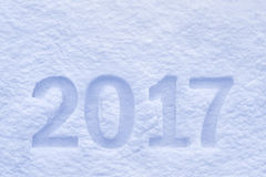 New Year 2017 greeting, 2017 numbers written on snow field, background Royalty Free Stock Photos